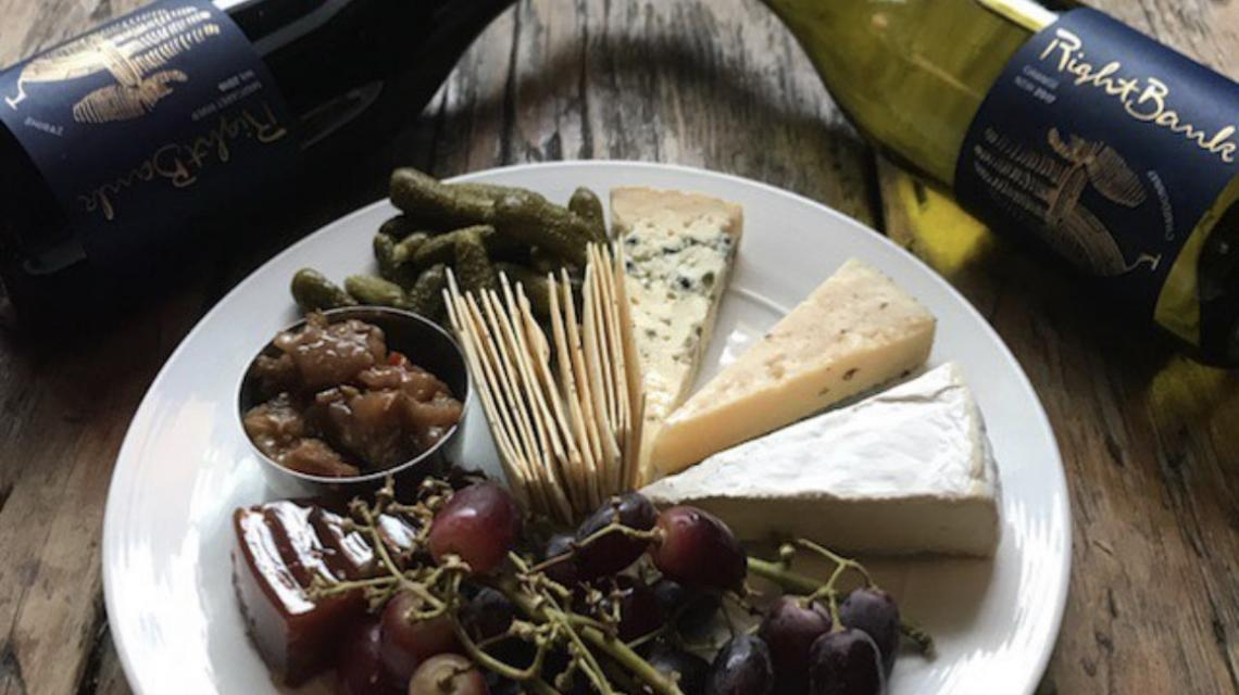 Picture of a cheese platter and two bottles of wine lying down.