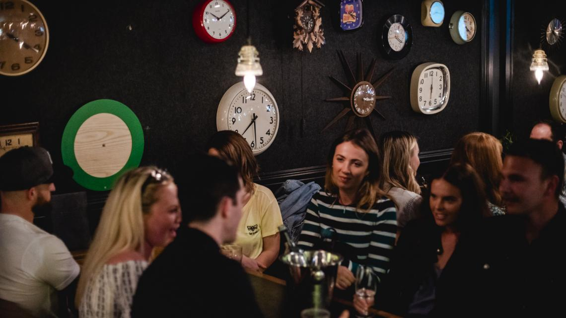 A couple of people sitting next to a wall of clocks in Street Bar